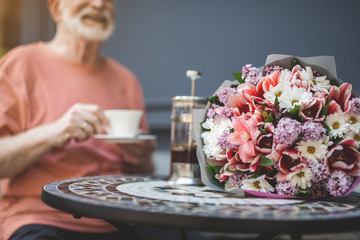 Focus on beautiful bunch of flowers lying on table in cafe. Senior male is sitting outside and drinking tea while waiting for his lady with joy