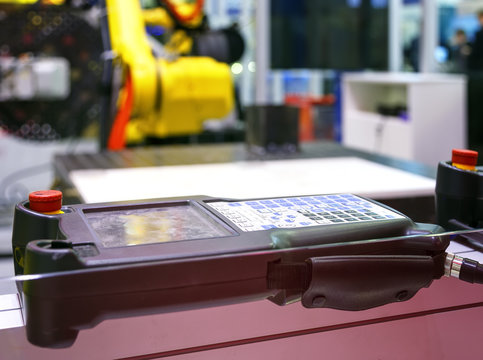 Digital Controller For Robot in Factory against the background of blurred yellow industrial robots