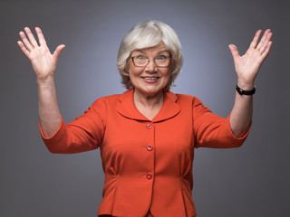 Happy senior lady with hands up