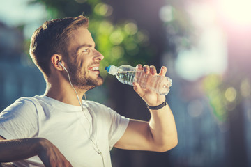 Profile of delighted smiling young athlete holding bottle of water in park. He is thirsty and content after tiring workout