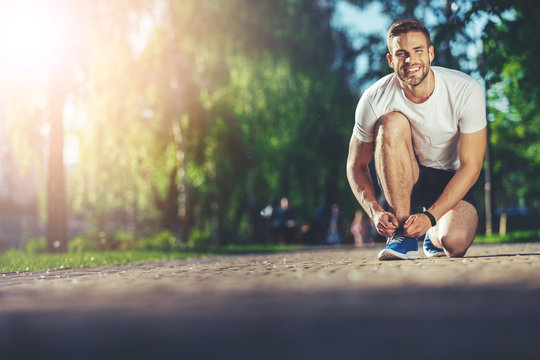 Full length portrait of smiling athlete kneeling and fixing shoelaces outdoors. He is joyfully looking at camera while listening to music with earphones. Copy space in left side
