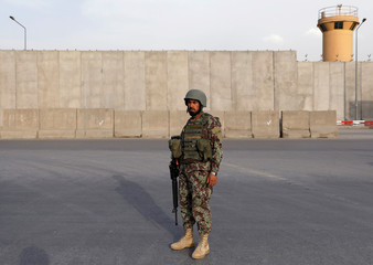 An Afghan National Army (ANA) soldier keeps watch near the site of a blast in Kabul