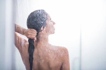 Side view orderly woman touching head and gesticulating arms while standing under stream of water