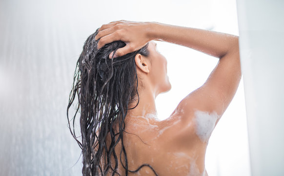 Girl using shampoo while taking shower in bright bathroom. She turning back to camera
