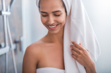 Outgoing girl wrapping in cozy towel with closing eyes after taking bath. She gesticulating hand