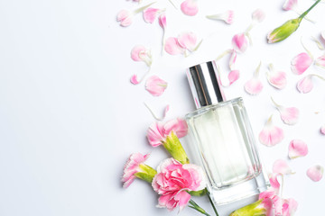 Perfume bottles and pink carnations on white background