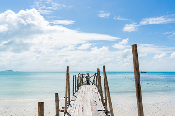 Old wooden pier leading out to the blue ocean