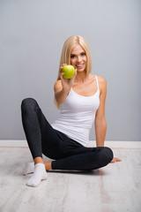 Woman sitting on floor, showing apple, against grey.