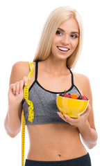 Woman in sportswear with tape measure and fruits, isolated