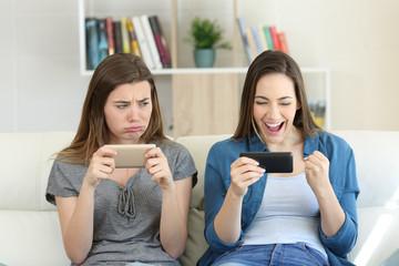 Envious loser girl looking at her winner friend