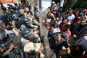 Protesters scuffle with security forces near the main provincial government building in Basra