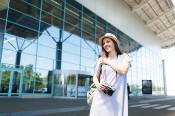 Young smiling traveler tourist woman in hat holding retro vintage photo camera, standing at international airport. Female passenger traveling abroad to travel on weekends getaway. Air flight concept.