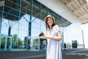 Young joyful traveler tourist woman holding retro vintage photo camera, looking aside at international airport. Female passenger traveling abroad to travel on weekends getaway. Air flight concept.
