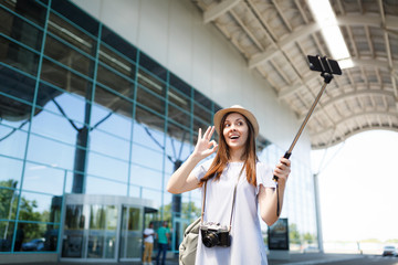 Young traveler tourist woman with retro vintage photo camera show OK sign doing selfie on mobile phone with monopod selfish stick at airport. Passenger traveling abroad on weekend. Air flight concept.