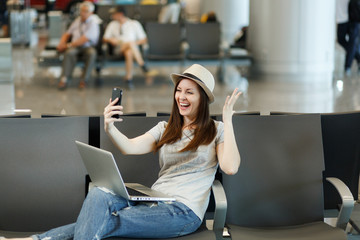 Laughing traveler tourist woman working on laptop, doing selfie on mobile phone, spreading hands, waiting in lobby hall at airport. Passenger traveling abroad on weekends getaway. Air flight concept.