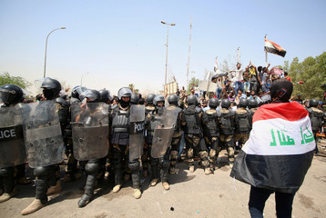 A protester wears an Iraqi flag in front of security forces during a protest near the main provincial government building in Basra