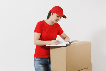 Delivery woman in red cap, t-shirt isolated on white background. Female courier holding filling clipboard with papers document, blank empty sheet on empty cardboard boxes. Receiving package Copy space