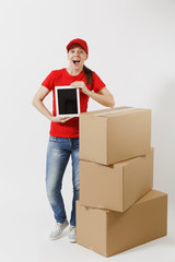 Full length of delivery young woman in red cap, t-shirt isolated on white background. Female courier near cardboard boxes, tablet pc computer, blank black empty screen. Receiving package. Copy space.