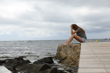 Profile of a depressed girl on the beach