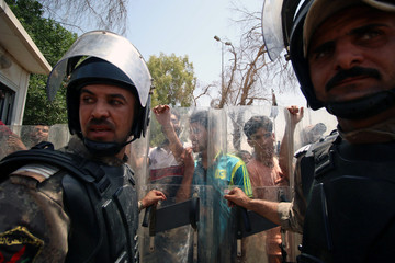 Iraqi security forces stand in front of protesters near the main provincial government building in Basra