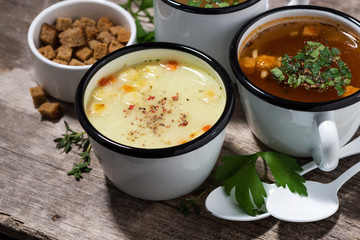 hot soups in mugs on wooden table