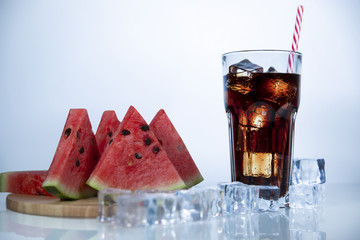 A refreshing drink of stake is poured into a glass beaker with a tube. Berry watermelon in water splashes. White background with scattered ice cubes.
