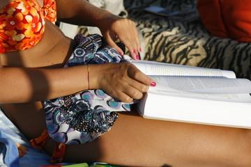 Ragazza legge libro sulla sdraio in spiaggia
