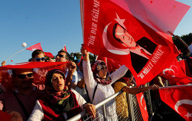 People wave Turkey's national flags and portraits of Turkish President Tayyip Erdogan as they arrive to attend a ceremony marking the second anniversary of the attempted coup at the Bosphorus Bridge in Istanbul