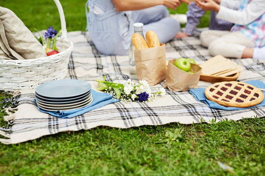 Stack of plates, bunch of wildflowers, cherry pie, fresh and crispbread, apples and busket with provisions on tablecloth on grass on background of family enjoying picnic