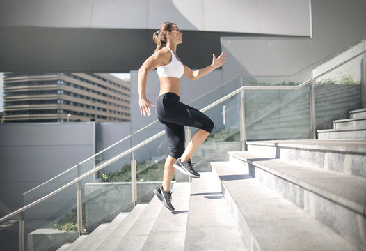 Sportive woman running on stairs in the street