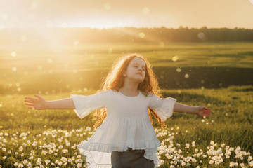 Curly hair girl closed her eyes and breathing with fresh blowing air on meadow outdoors.