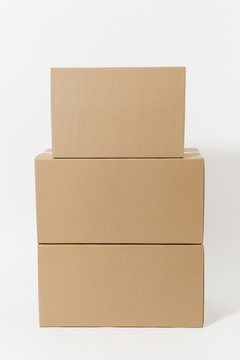 Stacked of three brown clear empty blank cardboard boxes isolated on white background. Receiving package. Copy space for advertisement. With place for text. Advertising area with workspace.