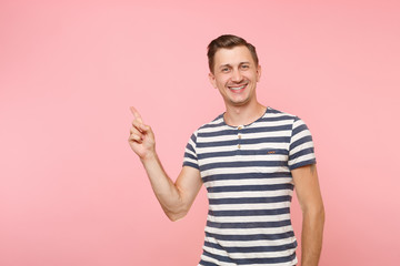Portrait excited smiling young man wearing striped t-shirt pointing index finger aside on copy space isolated on trending pink background. People sincere emotions lifestyle concept. Advertising area.
