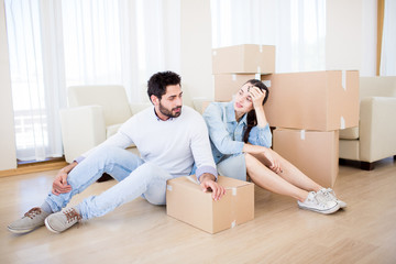 Young couple having rest on the floor of their new house by stack of boxes