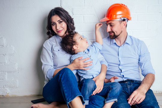 happy family handsome man in helmet hardhat and charming woman and their cute little son sitting on the floor against a white wall . concept of buying repairs house ( apartment ) by young family