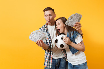 Young win couple, woman man, football fans holding bundle of dollars, cash money, soccer ball, cheer up support team isolated on yellow background. Sport bet, excitement ardor family lifestyle concept