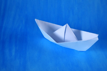 White paper ship against the blue background