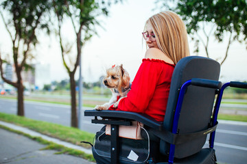 Beautiful young woman on a wheelchair enjoying outdoors with her dog.