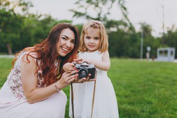Joyful woman in light dress and little cute child baby girl holding retro vintage photo camera in green park. Mother, little kid daughter. Mother's Day, love family, parenthood, childhood concept.