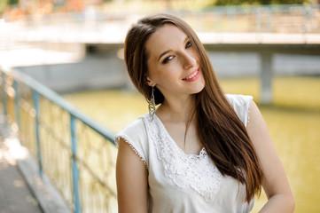Gorgeous smiling woman with dark hair in elegant white dress