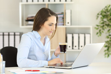 Office worker working online holding a coffee cup
