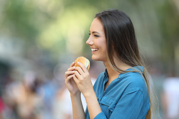 Profile of a woman holding a burger
