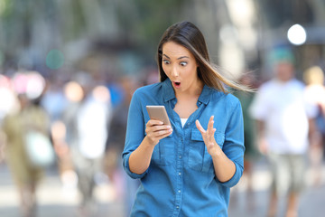 Shocked woman reading smart phone messages