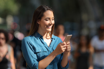 Smiley girl using a smart phone walking in the street