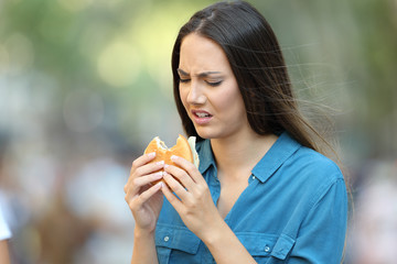 Woman eating a burger with bad taste