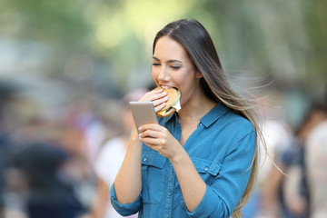Woman eating a burger holding a smart phone