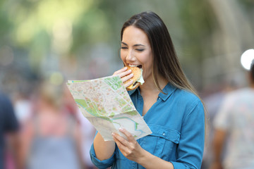 Woman eating burger and reading map on vacation