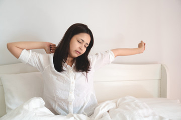 Young beautiful asian woman waking up in bed and stretching in bed in morning.
