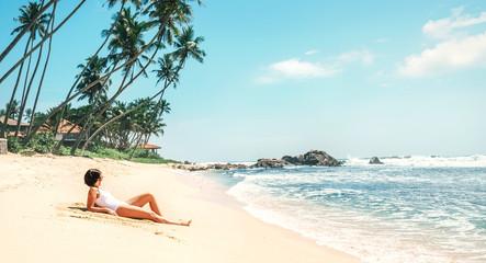 Woman takes sunbath on tropical beach