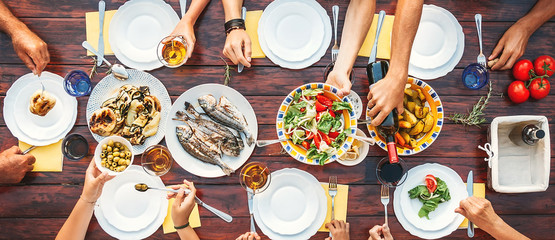 Big family dinner. Top vertical view on the table with dishes and hands